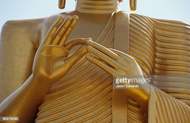 Closeup on the delicately arranged hands of the Golden Buddha statue.