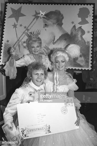 Dame Anna Neagle waves her magic wand over Paul Nicholas and Sarah Payne at the launch of the Post Office's Christmas stamps which have a pantomime...