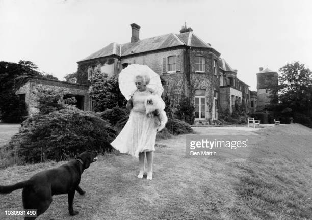 Dame Barbara Cartland English author of romance novels, strolling in the garden of her home in Camfield Place, Hertfordshire, September 19th, 1977.