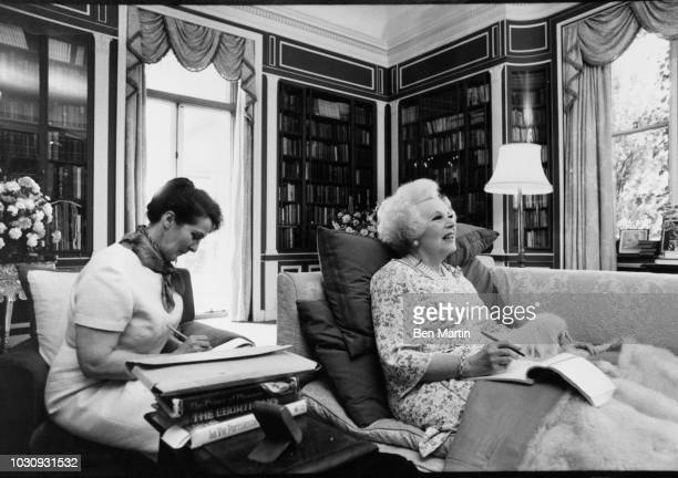 Dame Barbara Cartland English author of romance novels, writing with an assistants at home in Camfield Place, Hertfordshire, September 19th, 1977.