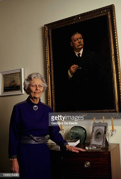 Dame Jean Conan Doyle daughter of Sir Arthur Conan Doyle poses in front of a portrait of her father the writer who created the fictional detective...