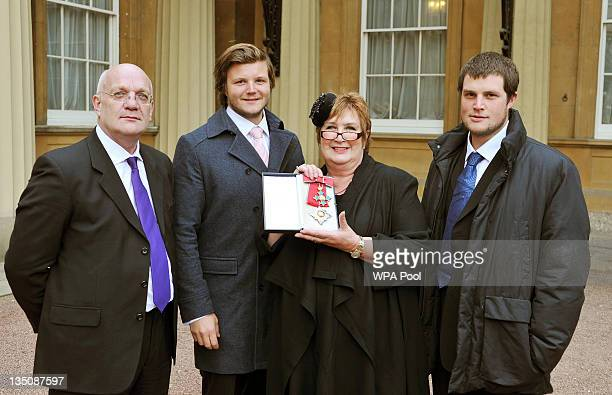 Dame Jenni Murray poses with husband David and sons Charlie and Ed after being made a Dame Commander by Queen Elizabeth II during an Investiture...
