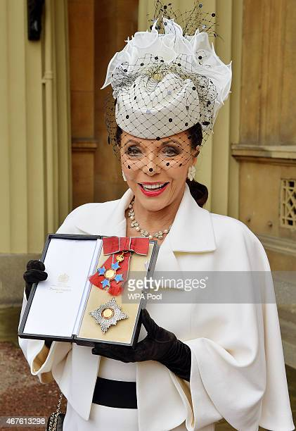 Dame Joan Collins holds her insignia of Dame Commander of the British Empire after being awarded by the Prince of Wales at an Investiture Ceremony at...