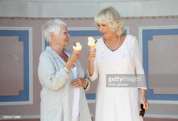 Dame Judi Dench and Camilla Duchess of Cornwall enjoy an ice cream at Queen Victoria's private beach next to Osborne House during a visit to the Isle...