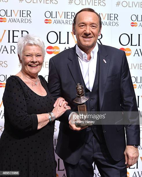 Dame Judi Dench and Kevin Spacey pose in the winners room at The Olivier Awards at The Royal Opera House on April 12 2015 in London England