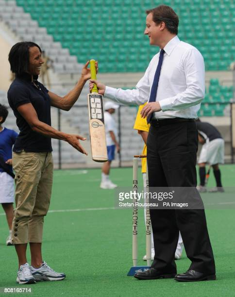 Dame Kelly Holmes passes a cricket bat to Prime Minister David Cameron during a visit to the Major Dhyan Chand National Hockey Stadium in Delhi on...
