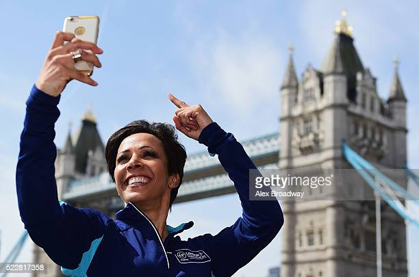 Dame Kelly Holmes poses for a selfi photograph in front of Tower Bridge as she attends a photocall ahead of the Virgin Money London Marathon at The...