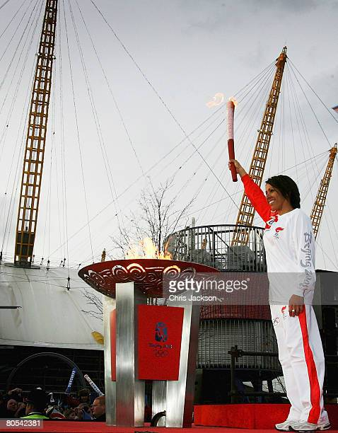 Dame Kelly Holmes stands with the Olympic Torch held aloft after completing the final leg of the Olympic Torch Relay at the O2 Dome on April 6 2008...