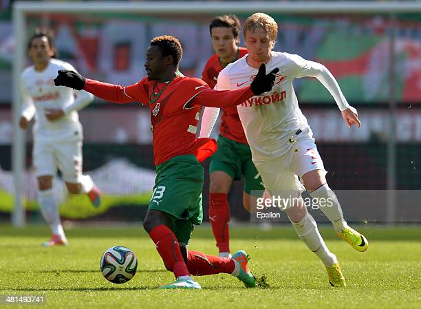 Dame N'Doye of FC Lokomotiv Moscow challenged by Sergei Bryzgalov of FC Spartak Moscow during the Russian Premier League match between FC Lokomotiv...