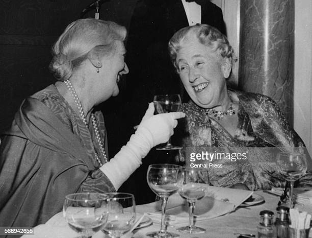 Dame Sybil Thorndike left talking to author Agatha Christie as they celebrate the opening of her first musical 'Vanity Fair' at the Ambassadors...