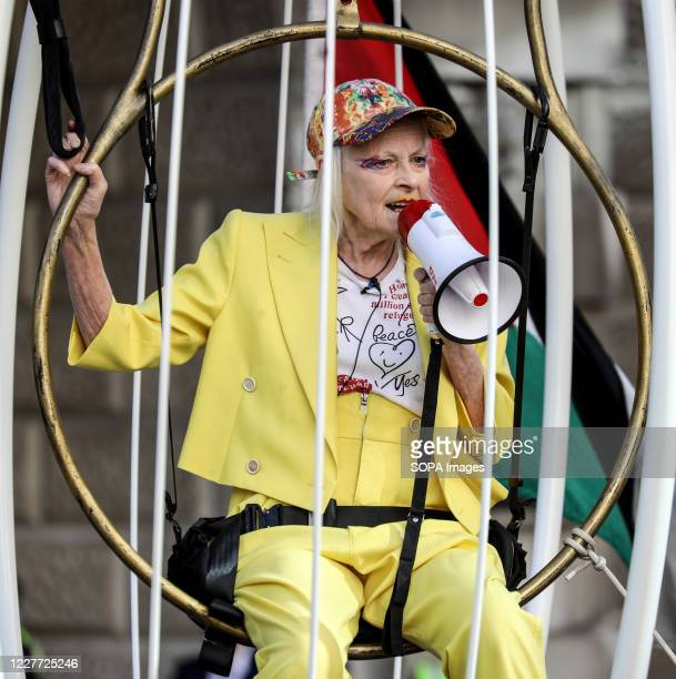Dame Vivienne Westwood addresses people using a mega phone inside a bird cage during the protest. Fashion designer and business woman Dame Vivienne...
