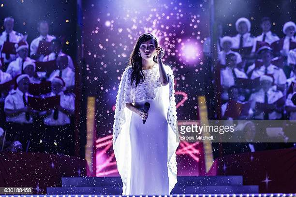 Dami Im waits to perform as rain pours down during the Woolworths Carols in the Domain at The Domain on December 18 2016 in Sydney Australia...