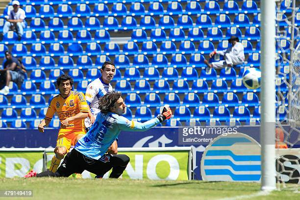 Damia‡n Alvarez of Tigres scores the goal of his team as Jorge Villalpando of Puebla falis to block during a match between Puebla and Tigres UANL as...