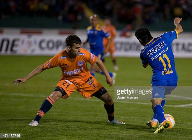 Dami‡an Alvarez of Tigres struggles for the ball with Ezequiel Filippetto of Universitario Sucre during a first leg match between Universitario Sucre...