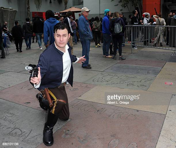 Damian Beurer of Legion M dressed as Han Solo posing on Harrison Ford's feet handprints in the courtyard at the Opening Night Celebrations Of Walt...