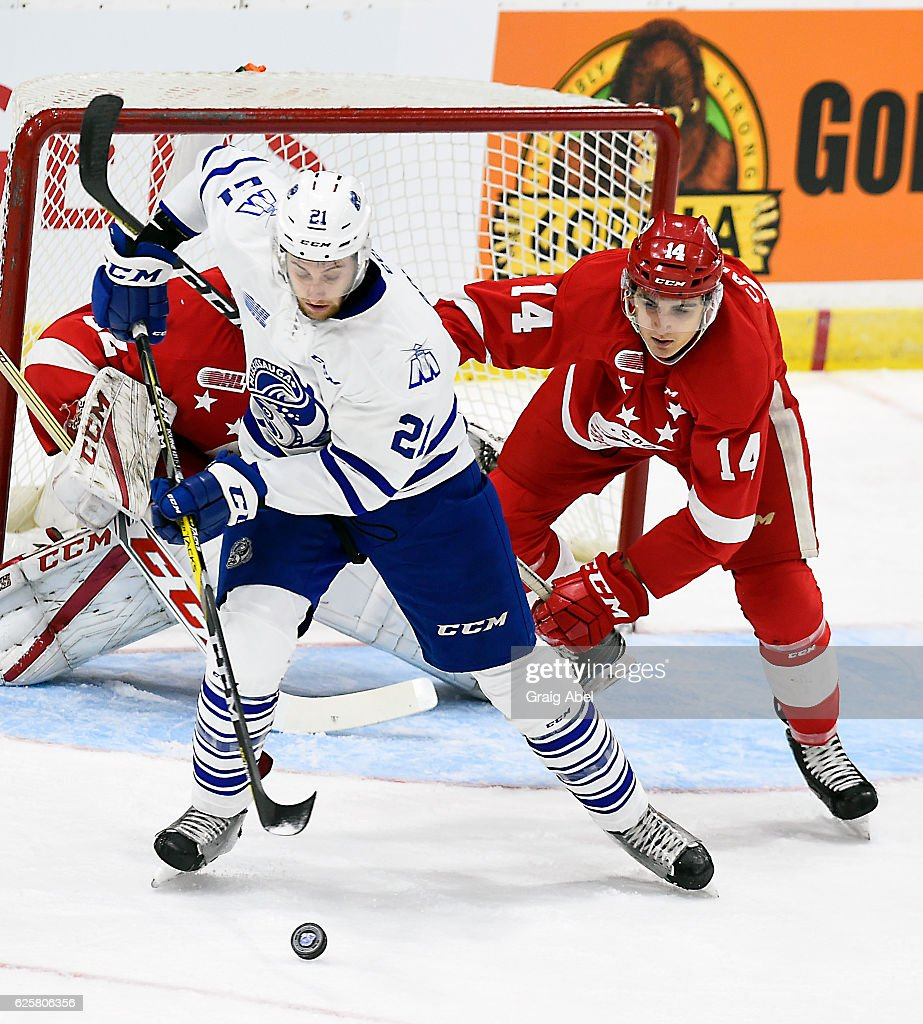 Damian Bourne #21 of the Mississauga Steelheads controls the puck against Theo Calvas #14 of the Sault Ste. Marie Greyhounds during game action on November 25, 2016 at Hershey Centre in Mississauga, Ontario, Canada.