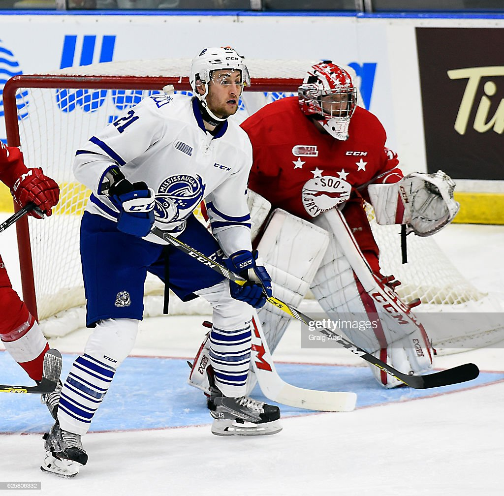 Damian Bourne #21 of the Mississauga Steelheads puts a screen on Joseph Raaymakers #32 of the Sault Ste. Marie Greyhounds during game action on November 25, 2016 at Hershey Centre in Mississauga, Ontario, Canada.