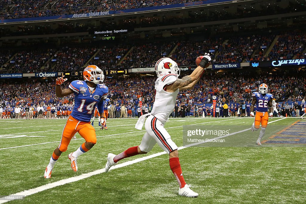 Damian Copeland #7 of the Louisville Cardinals catches a touchdown pass over Jaylen Watkins #14 of the Florida Gators in the third quarter of the Allstate Sugar Bowl at Mercedes-Benz Superdome on January 2, 2013 in New Orleans, Louisiana.