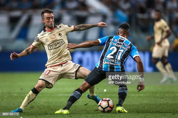 Damian Diaz of Ecuador's Barcelona vies for the ball with Fernandinho of Brazil's Gremio during their Copa Libertadores 2017 football match held at...