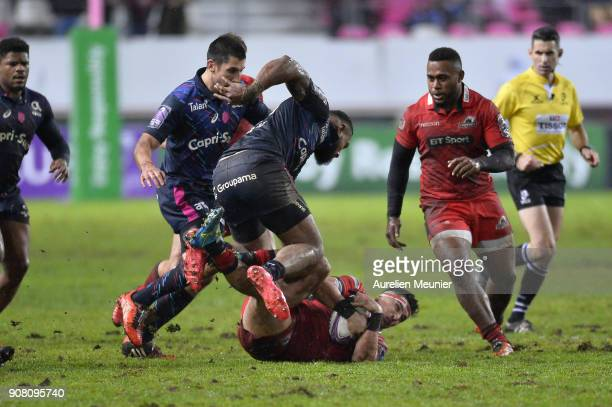 Damian Hoyland of Edinburgh is tackled by Waisea Nayacalevu of Stade Francais during the European Rugby Challenge Cup match between Stade Francais...