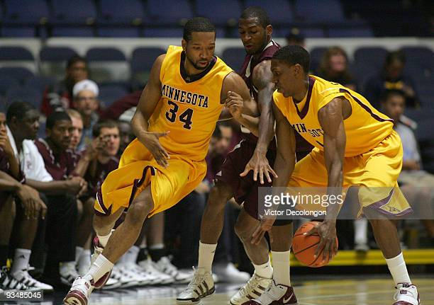 Damian Johnson of Minnesota runs to get the ball from teammate Paul Carter as Derrick Roland of Texas AM tries to defend the play in the first half...