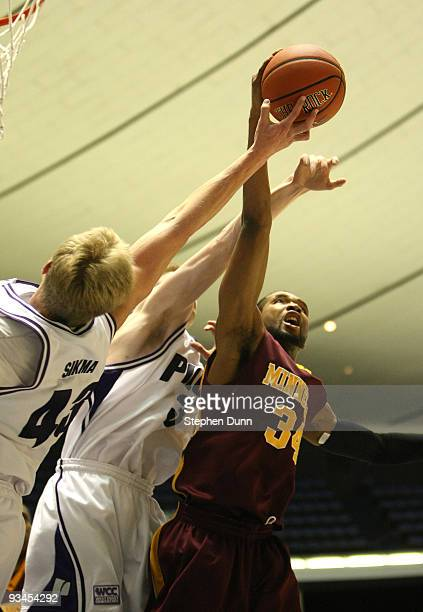 Damian Johnson of the Minnesota Gophers fights for a rebound with Luke Sikma of the Portland Pilots at the 76 Classic at Anaheim Convention Center on...