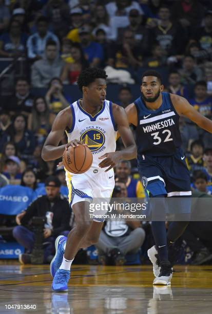 Damian Jones of the Golden State Warriors dribbles the ball while being guarded by KarlAnthony Towns of the Minnesota Timberwolves during an NBA...