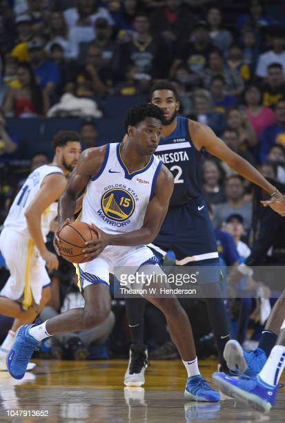 Damian Jones of the Golden State Warriors looks to pass the ball while being guarded by KarlAnthony Towns of the Minnesota Timberwolves during an NBA...