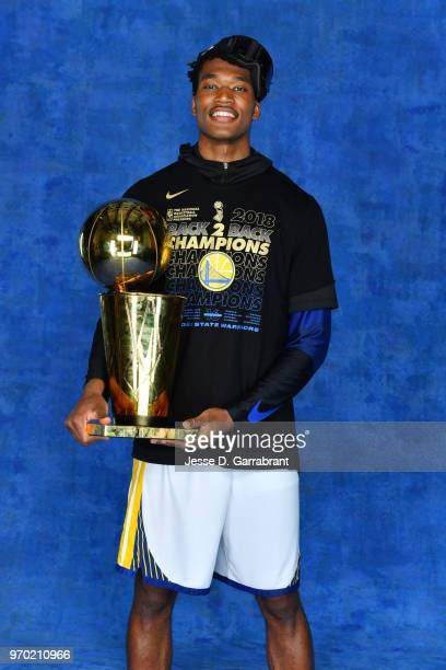 Damian Jones of the Golden State Warriors poses for a portrait with the Larry O'Brien Championship trophy after defeating the Cleveland Cavaliers in...
