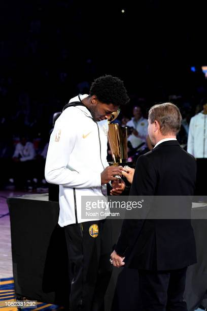 Damian Jones of the Golden State Warriors receives his 2018 NBA Finals Championship ring from Owner Peter Guber on October 16 2018 at Oracle Arena in...
