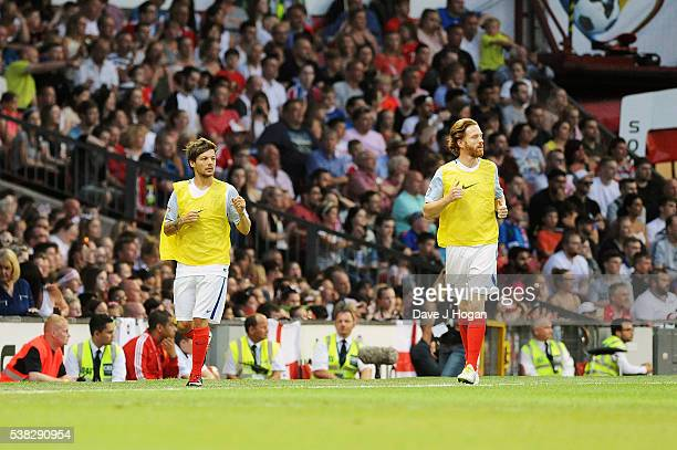 Damian Lewis and Louis Tomlinson warm up during Soccer Aid at Old Trafford on June 5, 2016 in Manchester, England.