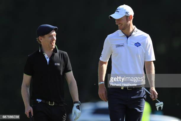 Damian Lewis walks with Chris Wood of England during the BMW PGA Championship ProAm at Wentworth on May 24 2017 in Virginia Water England