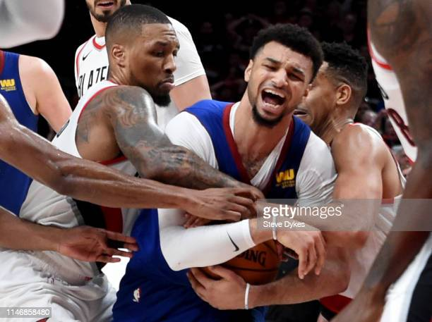 Damian Lillard and CJ McCollum of the Portland Trail Blazers tie up Jamal Murray of the Denver Nuggets during the third overtime of game three of the...