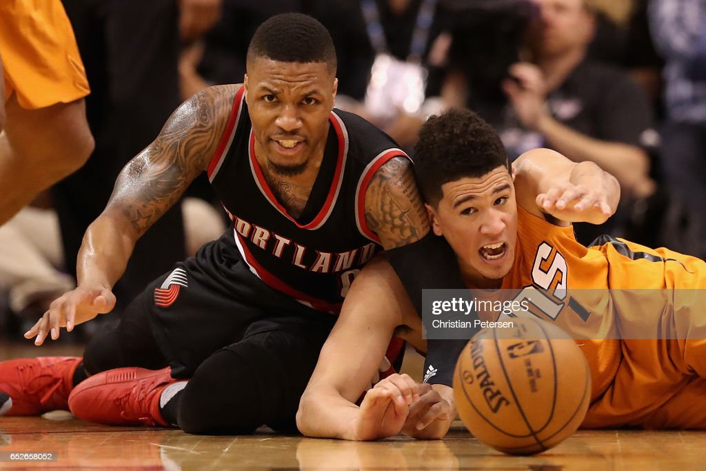 Damian Lillard #0 of the Portland Trail Blazers and Devin Booker #1 of the Phoenix Suns reach for a loose ball during the second half of the NBA game at Talking Stick Resort Arena on March 12, 2017 in Phoenix, Arizona. The Trailblazers defeated the Suns 110-101.