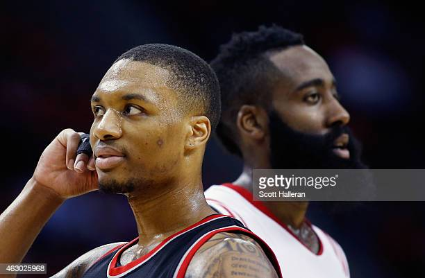 Damian Lillard of the Portland Trail Blazers and James Harden of the Houston Rockets walk across the court during their game at the Toyota Center on...
