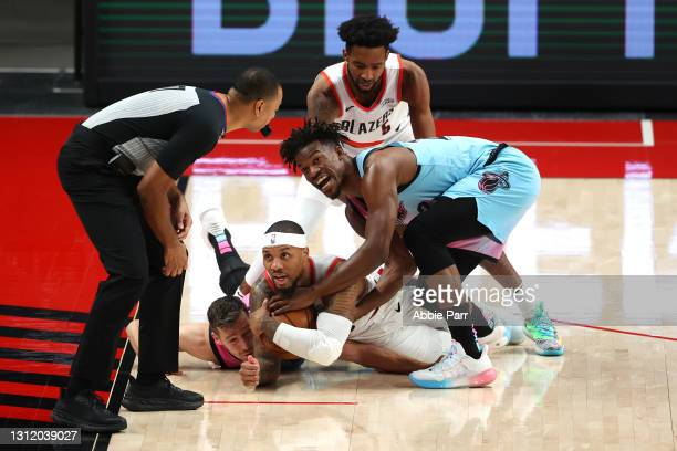 Damian Lillard of the Portland Trail Blazers and Jimmy Butler of the Miami Heat react to a jump ball call by the official in the first quarter at...
