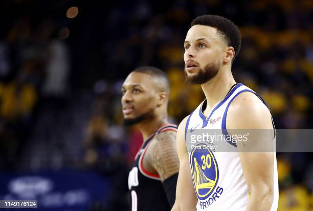 Damian Lillard of the Portland Trail Blazers and Stephen Curry of the Golden State Warriors look on during the second half in game one of the NBA...