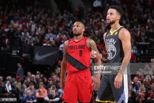 Damian Lillard of the Portland Trail Blazers and Stephen Curry of the Golden State Warriors look on during the game between the two teams on February...