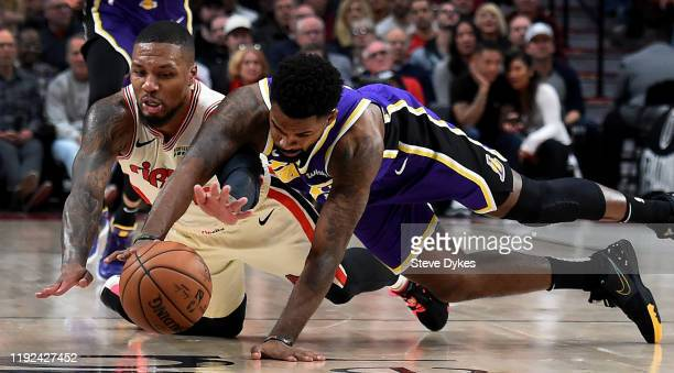 Damian Lillard of the Portland Trail Blazers and Troy Daniels of the Los Angeles Lakers go after a loose ball during the second half of the game at...