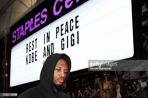 Damian Lillard of the Portland Trail Blazers arrives for the game against the Los Angeles Lakers as he passes a sign to honor Kobe and Gigi Bryant at...