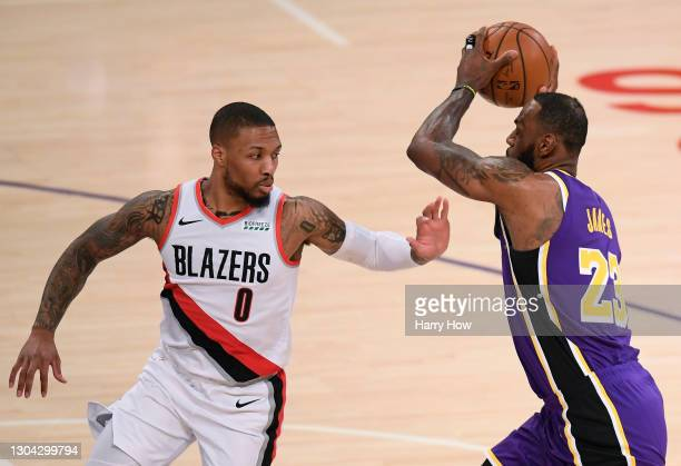 Damian Lillard of the Portland Trail Blazers attempts to slow LeBron James of the Los Angeles Lakers as he drives to the basket during the first...