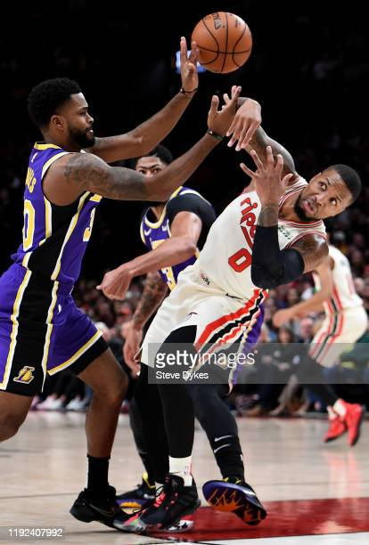 Damian Lillard of the Portland Trail Blazers battles for a loose ball with Troy Daniels of the Los Angeles Lakers during the first half of the game...