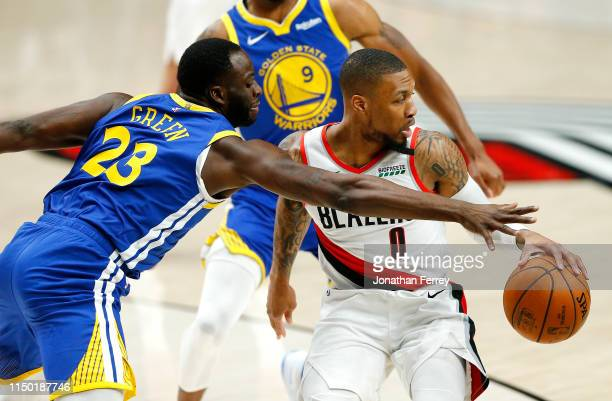 Damian Lillard of the Portland Trail Blazers battles for the ball with Draymond Green of the Golden State Warriors during the first half in game...