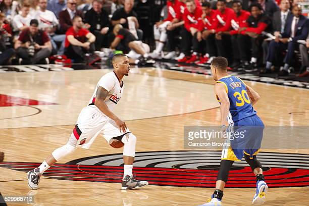 Damian Lillard of the Portland Trail Blazers brings the ball up court against Stephen Curry of the Golden State Warriors in Game Four of the Western...