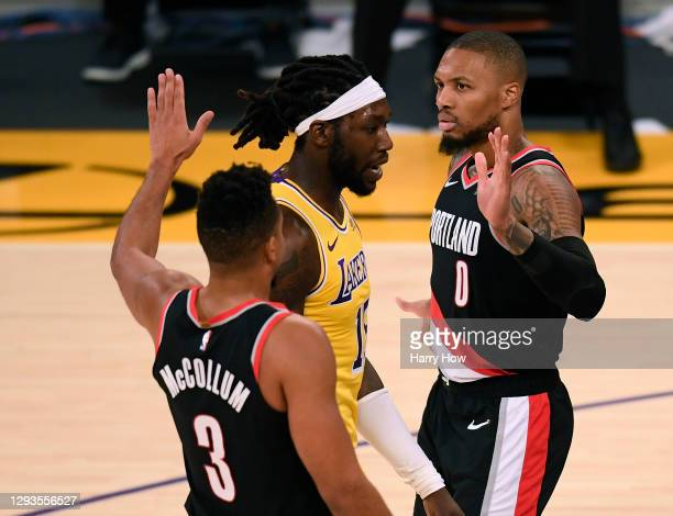Damian Lillard of the Portland Trail Blazers celebrates his basket with a foul with CJ McCollum, as Montrezl Harrell of the Los Angeles Lakers...
