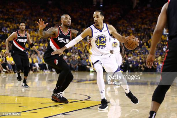 Damian Lillard of the Portland Trail Blazers defends Shaun Livingston of the Golden State Warriors during the first half in game one of the NBA...