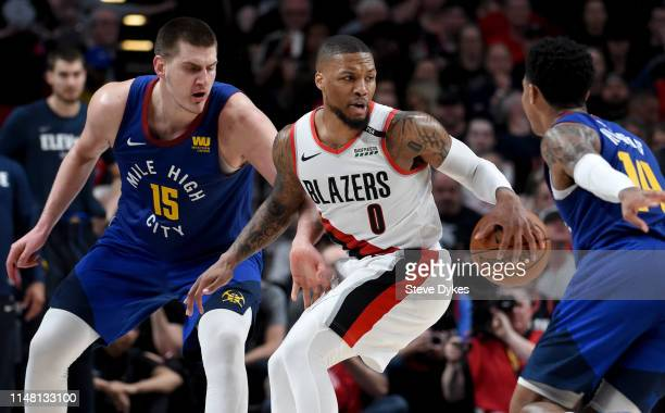 Damian Lillard of the Portland Trail Blazers does a spin move on Nikola Jokic and Gary Harris of the Denver Nuggets during the second half of Game...