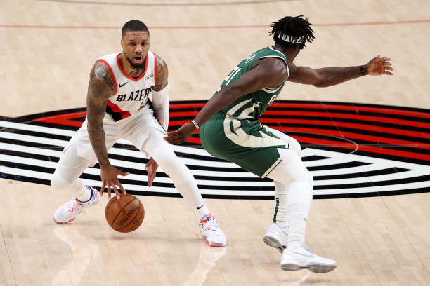 Damian Lillard of the Portland Trail Blazers dribbles against Jrue Holiday of the Milwaukee Bucks in the first quarter at Moda Center on April 02,...