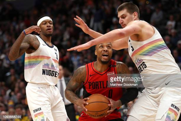 Damian Lillard of the Portland Trail Blazers drives against Nikola Jokic of the Denver Nuggets at the Pepsi Center on January 13 2019 in Denver...