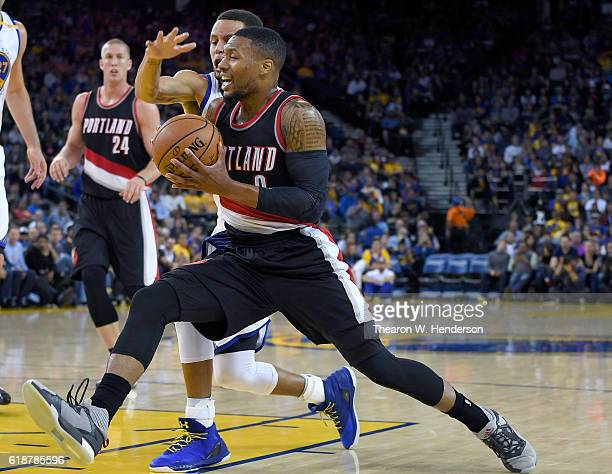 Damian Lillard of the Portland Trail Blazers drives on Stephen Curry of the Golden State Warriors during an NBA basketball game at ORACLE Arena on...